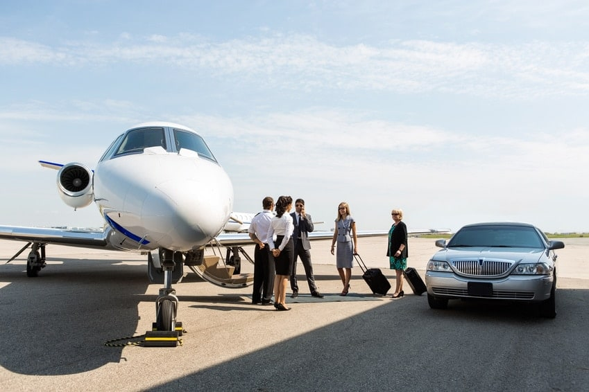 business people standing near private jet and limo